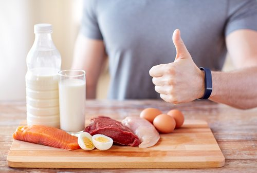 close up of man with food rich in protein showing thumbs up
